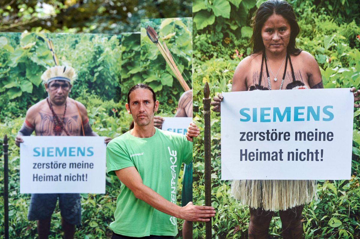 """Greenpeace bringt im Juli 2016 die Gesichter der Betroffenen nach Deutschland – vor die Zentrale von Siemens. Aktivisten fordern vom Konzern ein klares """"nein"""" zur Urwaldzerstörung."""