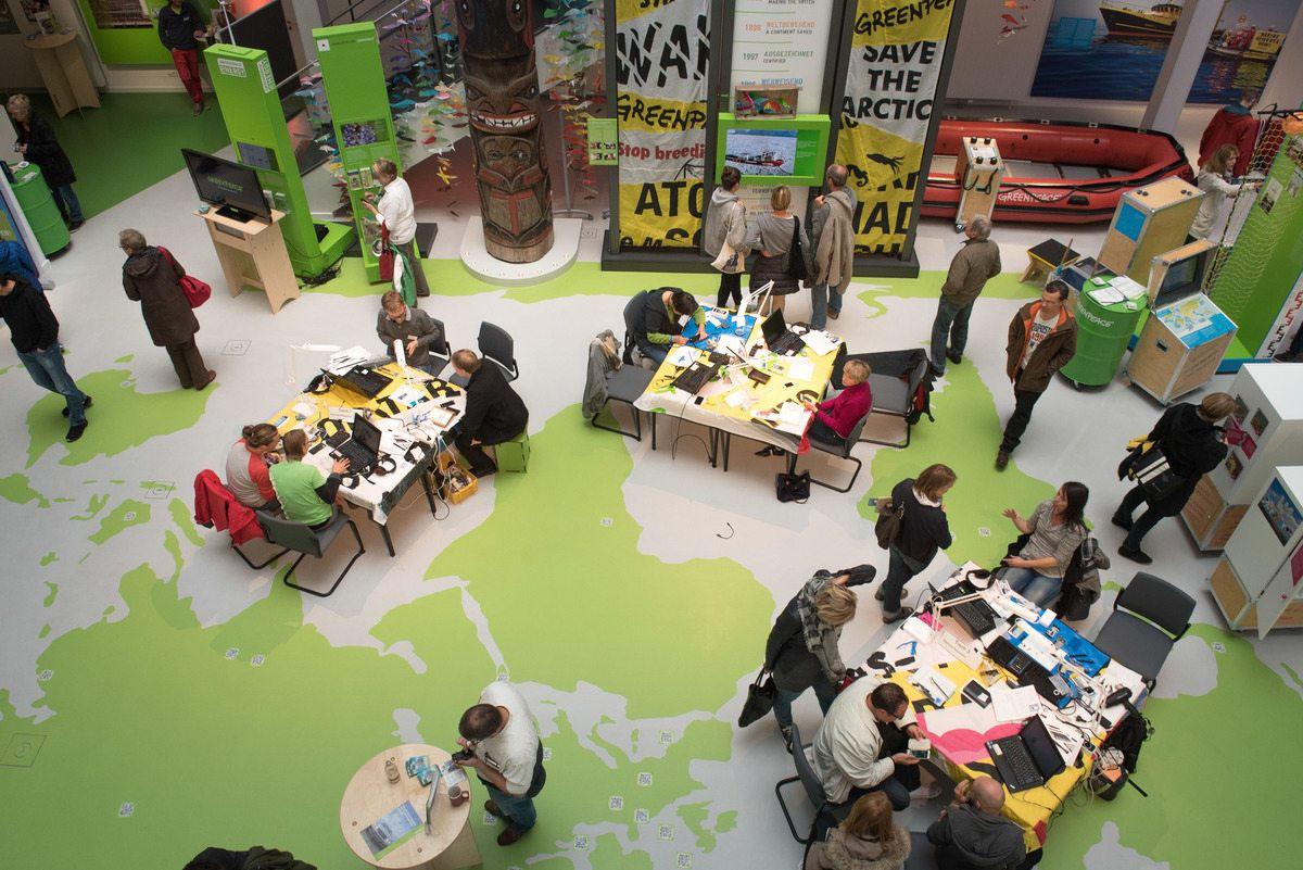 Konzentrierte Atmosphäre im Atrium des Greenpeace-Büros in Hamburg: Im Repair Café können – unter fachlicher Anleitung – defekte Geräte repariert werden. Zusätzlich gibt es eine Ausstellung zu den Themen Elektroschrott und Grüne Elektronik und mehrere Vorträge.