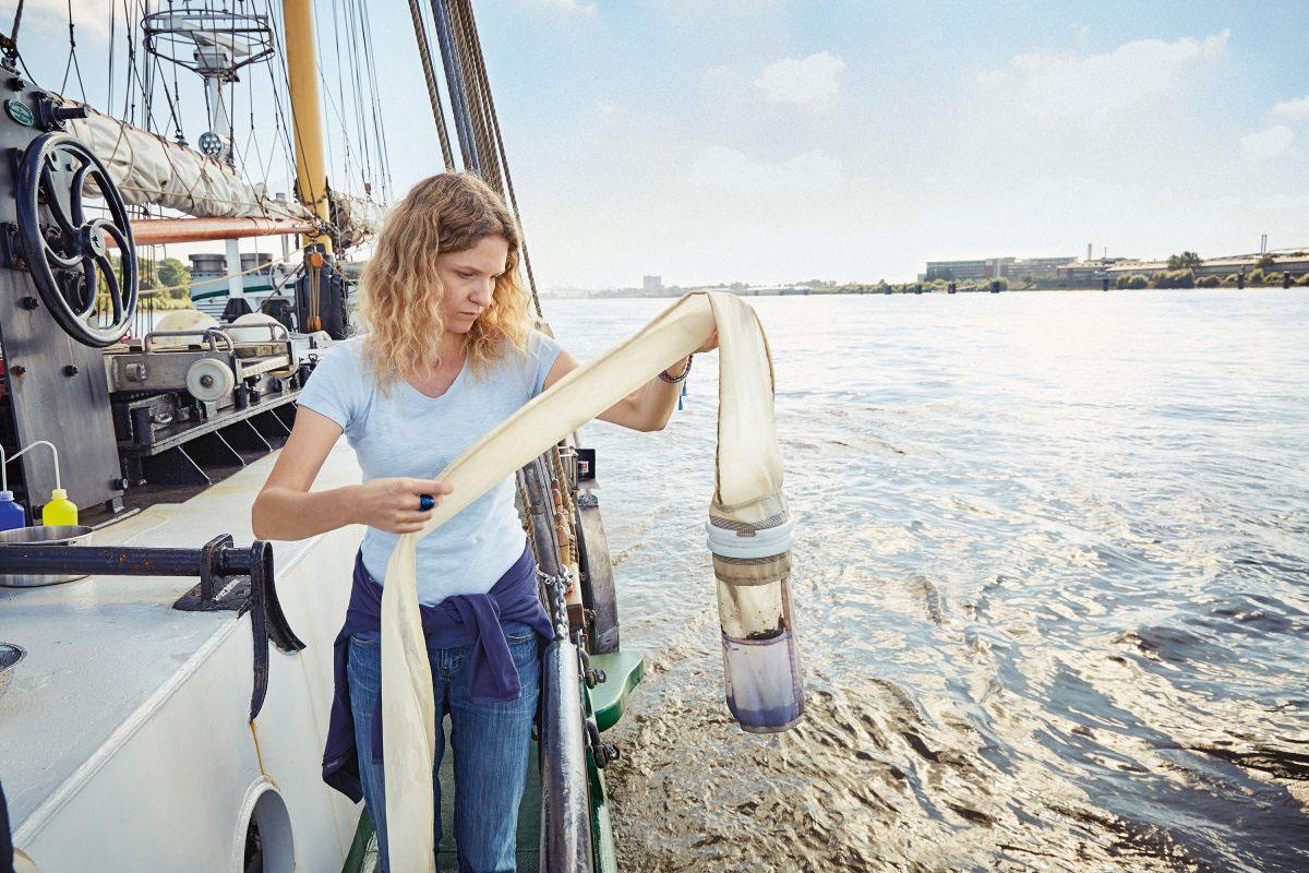 Dr. Sandra Schöttner, Meeresexpertin bei Greenpeace, untersucht vorsichtig das Netz des Manta Trawls, das winzige Partikel aus der Elbe gefischt hat.