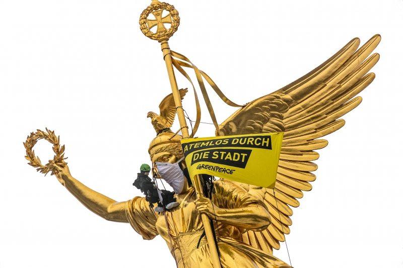 """Protest in luftiger Höhe: Zum Schutz vor Diesel-Abgasen bindet ein Greenpeace-Aktivist der """"Goldelse"""" eine  Atemschutzmaske um."""