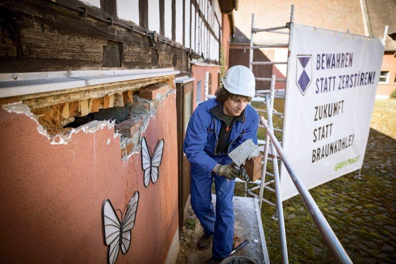 Greenpeace-Aktivisten bauen Gerüste auf und reparieren aufgeschlagene Wände, um die denkmalgeschützten Gebäude vor dem Verfall zu bewahren.