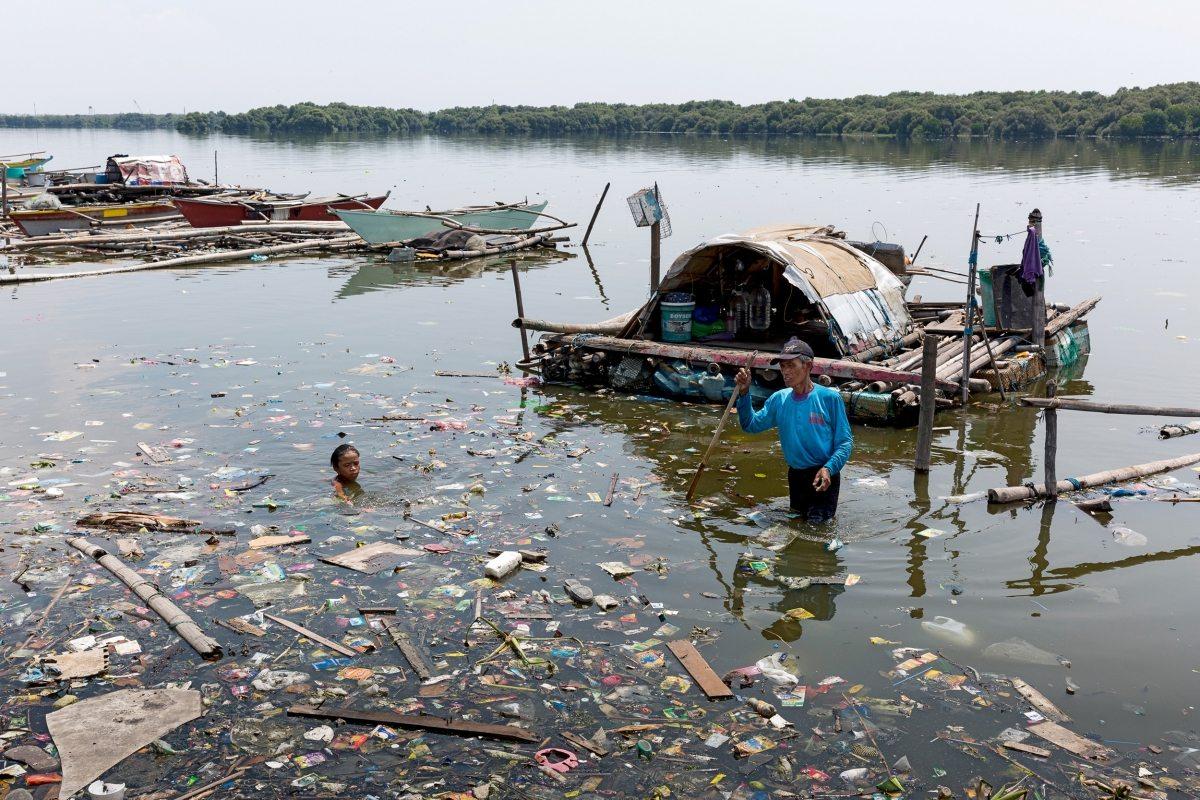 """Vor der gesperrten Vogelschutzinsel """"Freedom Island"""" baden Kinder im verdreckten Meer. Der Fang der Fischer wird auf lokalen Märkten verkauft."""