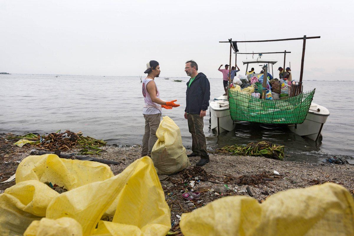 """Kampaigner Michael Meyer-Krotz (vorne rechts) spricht mit einem Helfer. Das Team von Greenpeace Ostasien ist sehr aktiv im """"Break free from Plastic""""-Bündnis, das auch die Bucht von Plastik säubert."""