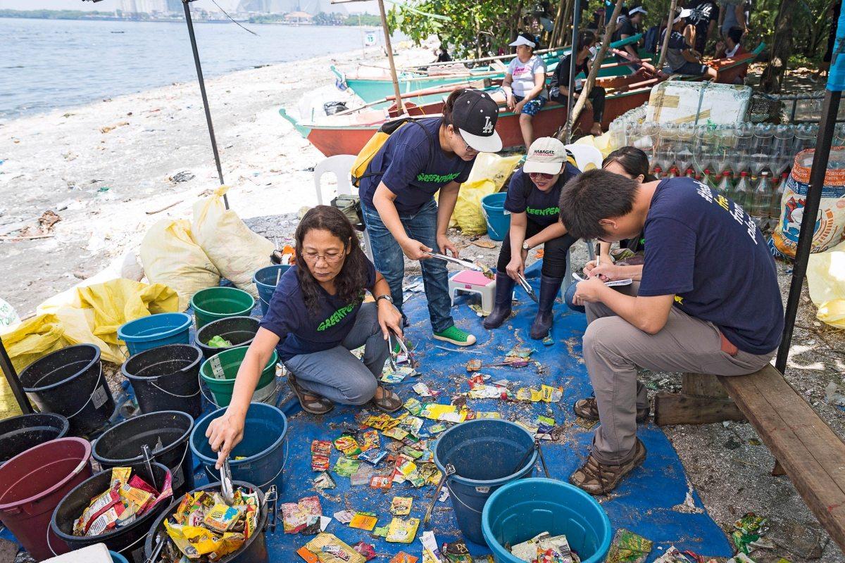 Greenpeace-Aktivisten sortieren Plastikteile nach Herstellern, um eine repräsentative Stichprobe zu erhalten.