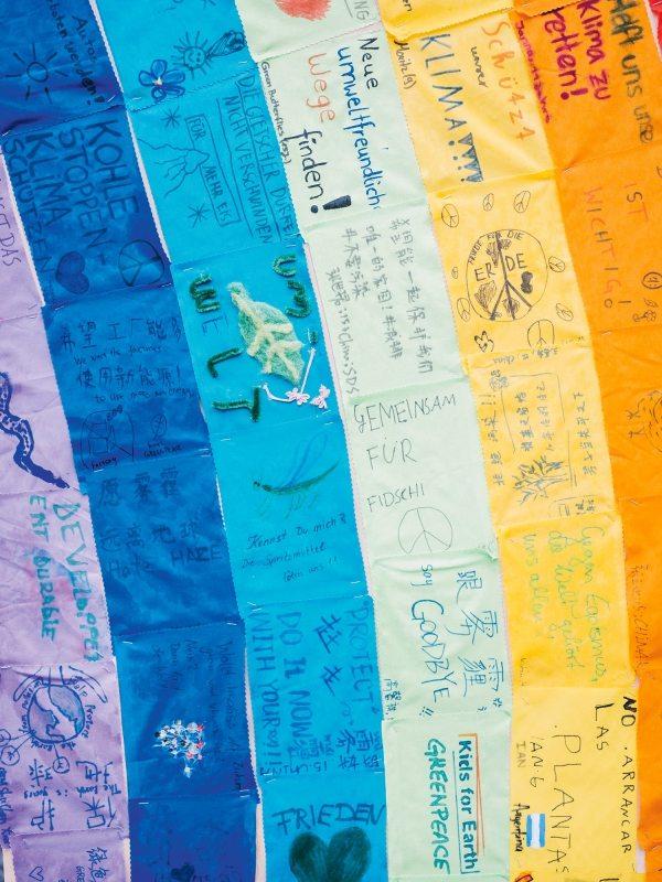 Kinder aus aller Welt haben bunte Stoffe mit ihren Botschaften und Forderungen bemalt.