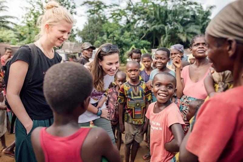 Gemeinsam sprechen Capucine Dayen von Greenpeace Afrika (Mitte) und eine norwegische Journalistin, die sie begleitet, mit den Kindern des Dorfes über den Schutz des Klimas.