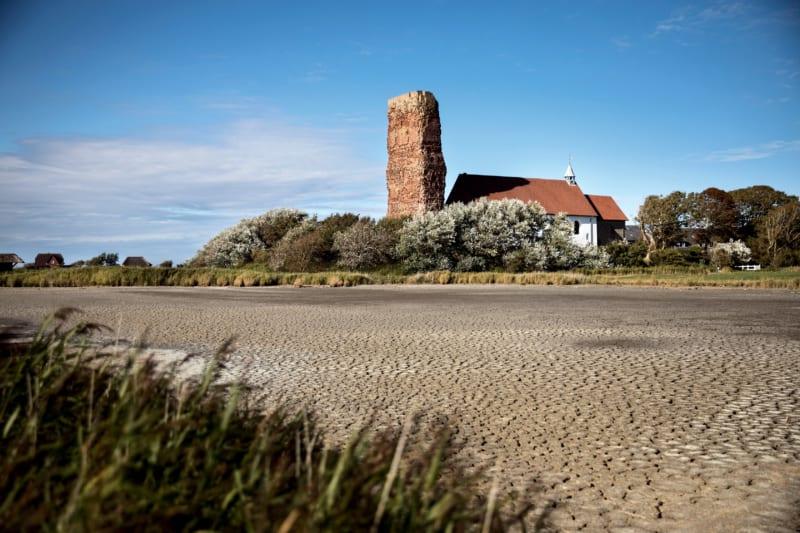 Viele Teiche und Bäche – wie hier vor der eingestürzten alten Kirche am Weststrand der Nordseeinsel – sind in diesem Hitzesommer ausgetrocknet