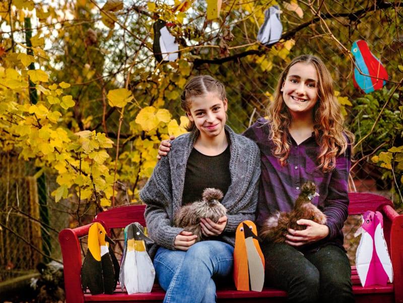 Nele Benta (14) und Edda Lou Lieber (15) im Edinger Kleintierzuchtverein, wo sie sich um Zwergseidenhühner kümmern – die Namensgeberinnen ihres Greenteams. Außerdem setzen sie einige der 2500 Pinguine ins Bild, die Kinder für den Antarktisschutz gebastelt haben
