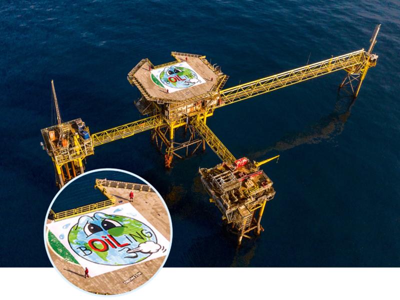 """Auf dem Helideck der """"Dan-Bravo""""-Ölplattform entfalten die Aktivistin und die drei Aktivisten ein riesiges Banner mit einer schwitzenden Erde, das der dänische Streetart Künstler HuskMitNavn entworfen hat"""