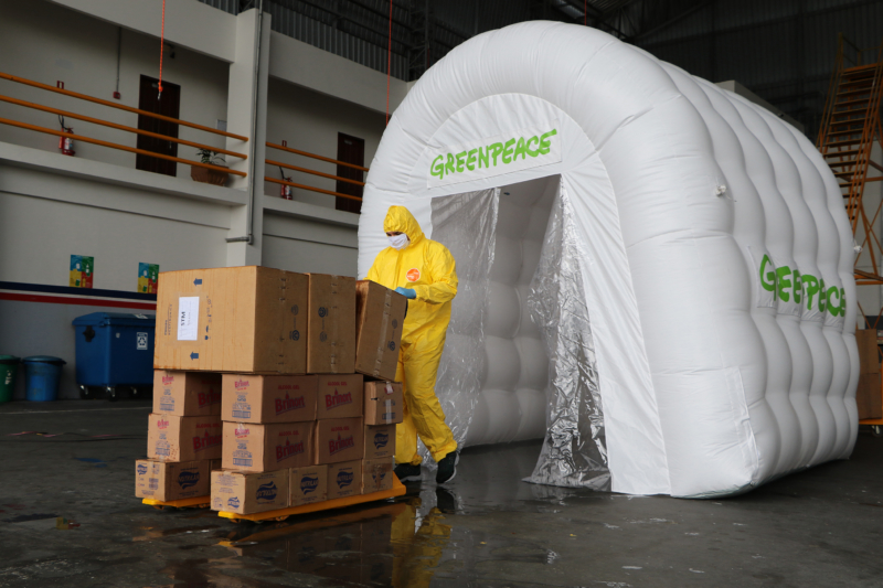 Am Flughafen in Manaus desinfizierten Greenpeace-Aktive Hygiene- und Hilfsmittel vor der Auslieferung (unten) in einer Ozonschleuse der Organisation